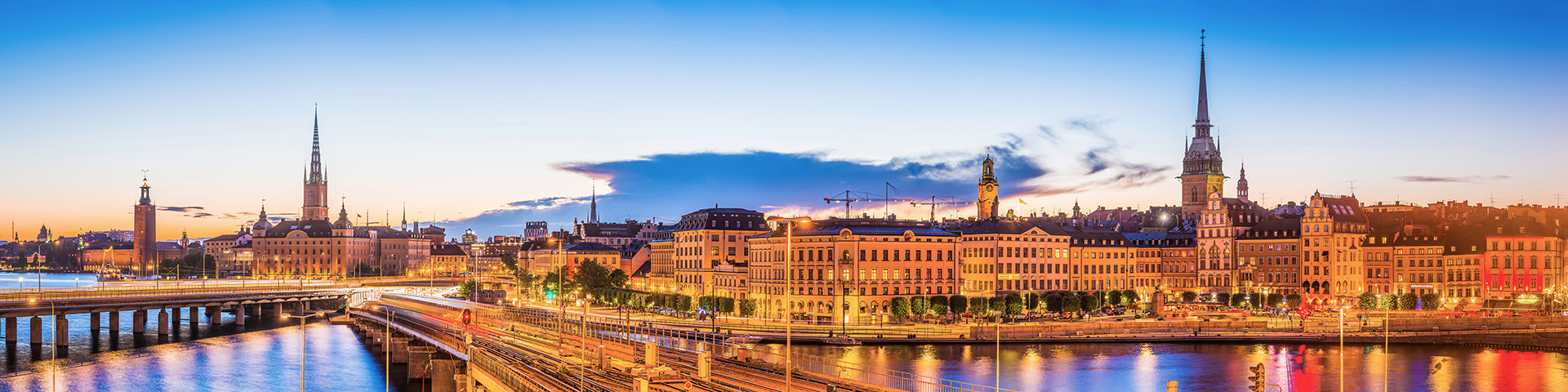 Clear blue summer sunset skies framing the landmarks of Stockholm, Sweden's vibrant capital city, from the iconic bell tower of City Hall to the colourful lights and iconic historic townhouses, restaurants and bars of Gamla Stan.